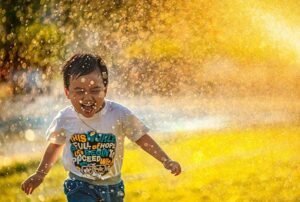 A happy child plays outside in the water on a warm day